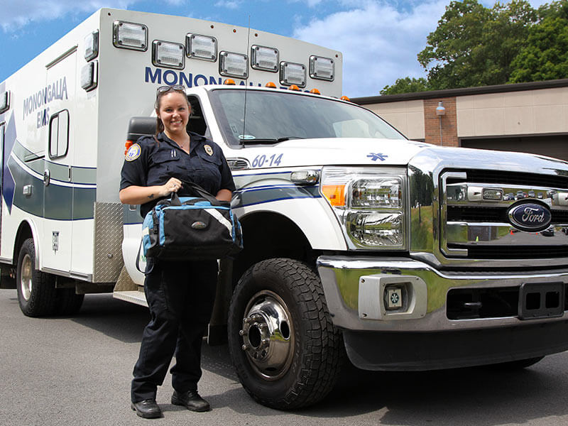 A Mon EMS paramedic standing in front of an ambulance